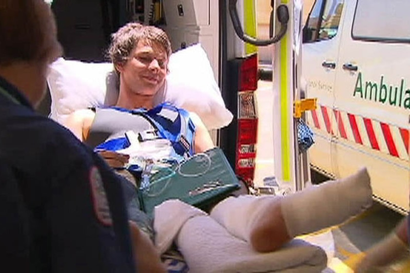 TV still: A young South Australian man is wheeled out of an ambulance after shark attack.