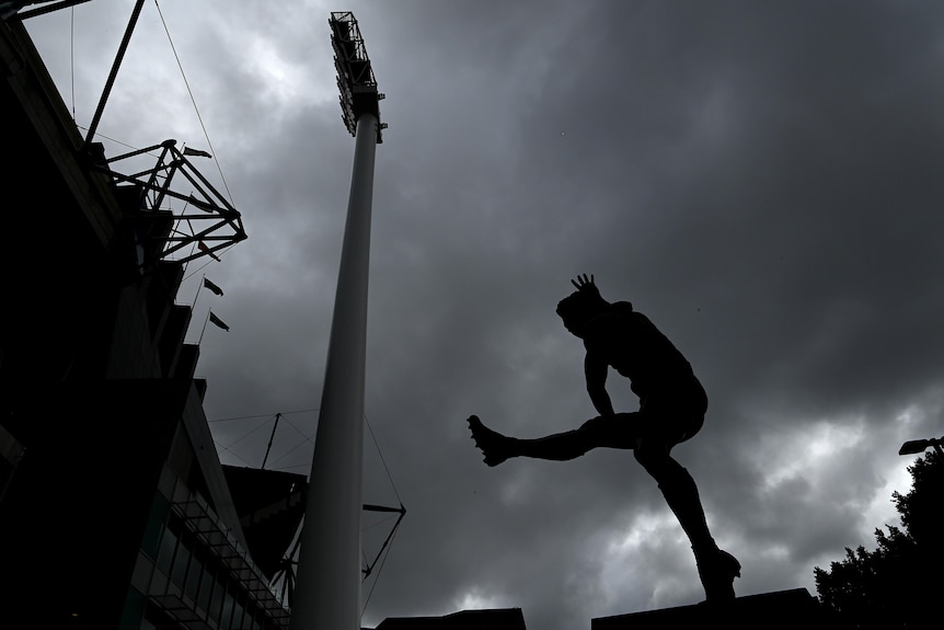 The statue of Ron Barassi is seen outside the MCG with a backdrop of grey, cloudy skies.