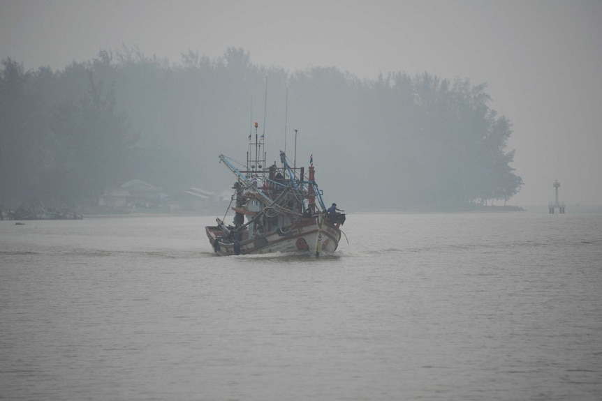A fishing boat sails on the Narathiwat river through haze in southern Thailand