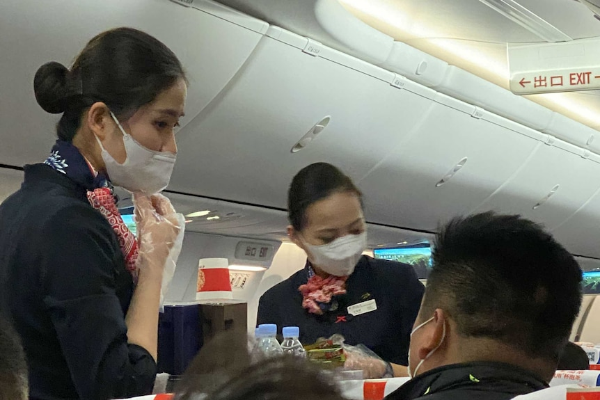 Flight attendants wearing masks inside plane.