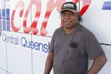 An Aboriginal man wearing a cap and a big smile stands in front of a sign that says Anglicare Central Queensland.