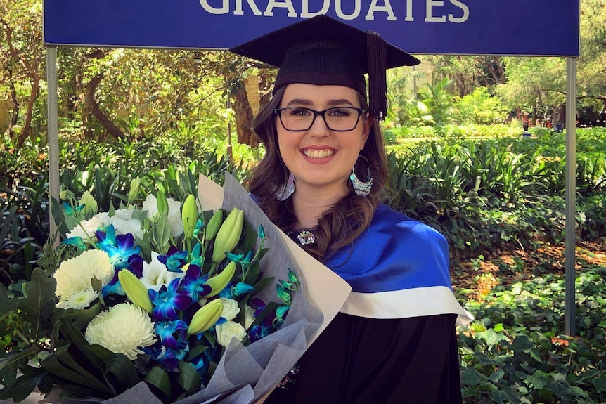 Drisana is wearing a mortarboard and university robes and holding a large bunch of flowers at her uni graduation.