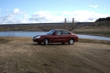 A car parked at the bottom of Wyangala Dam near Cowra NSW shows how low the storage has fallen in recent years