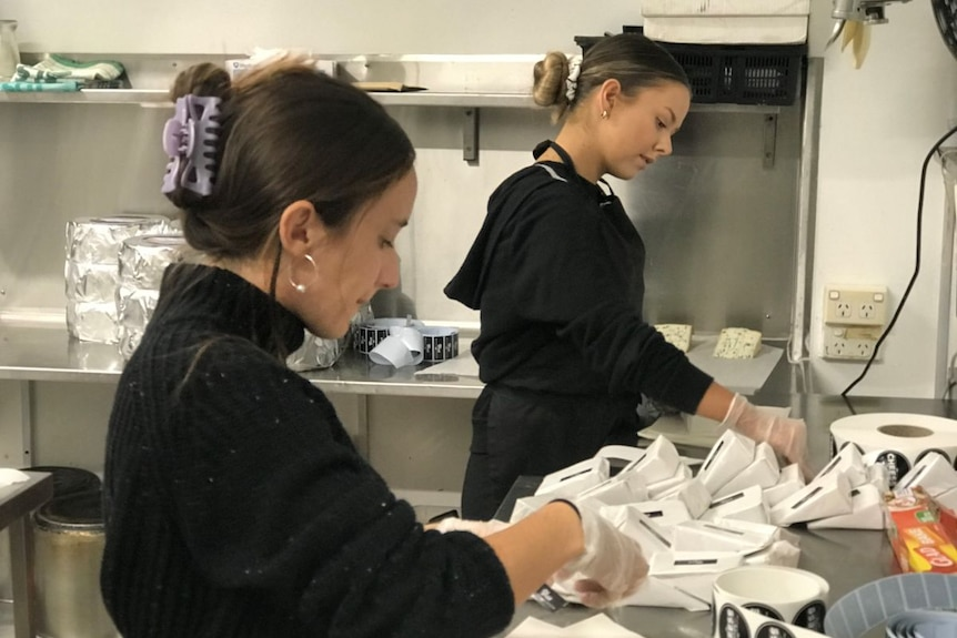 Two women wearing black pack cheese in white paper.