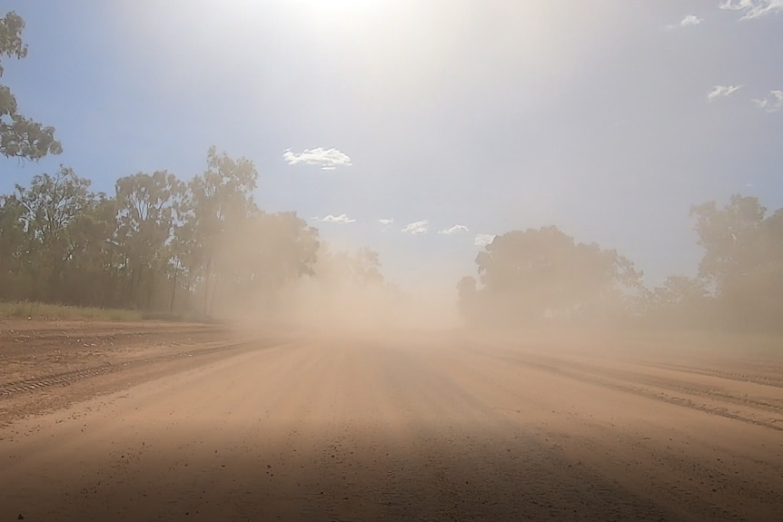 a dirt road is dusty after a truck passed