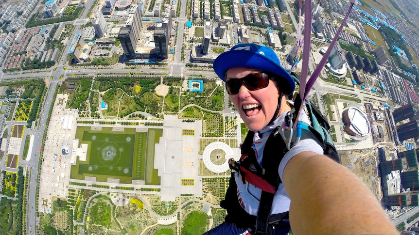 A woman in a helmet skydiving over a city.