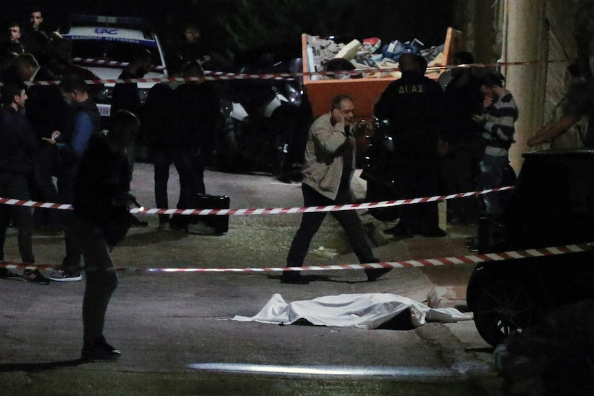 A cadaver is covered by a sheet and guarded by police on the side of a dark road near a construction skip bin