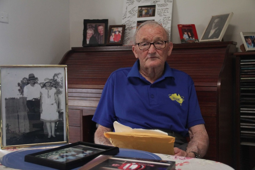 An older man with glasses and a blue shirt, sitting at a table with photos and documents.