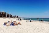 People sunbaking at Glenelg Beach.