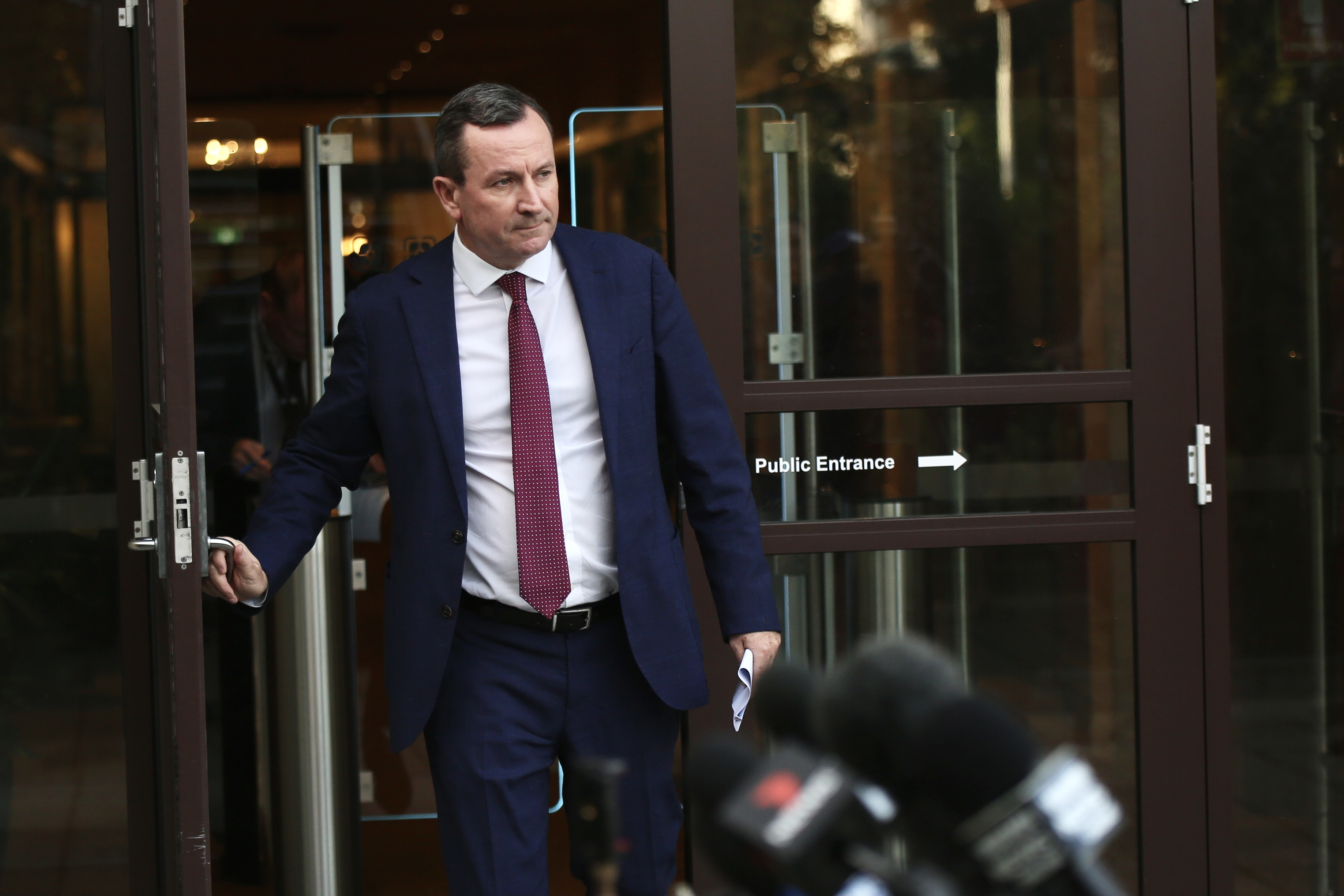 The Premier Mark McGowan wearing a suit with a red tie opens a glass door into a court yard with waiting microphones in the fore