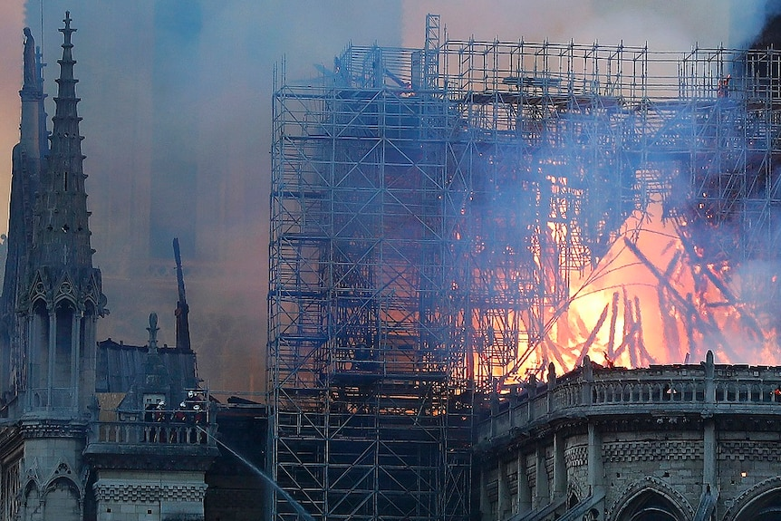 The spire of a gothic cathedral burns along with scaffolding while thick smoke fills the sky