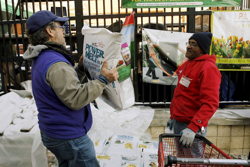 A customer carries out a bag of ice melt from a hardware store in Maryland.