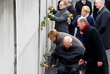 A group of leaders including the German Chancellor and President place yellow and orange at the Berlin Wall memorial