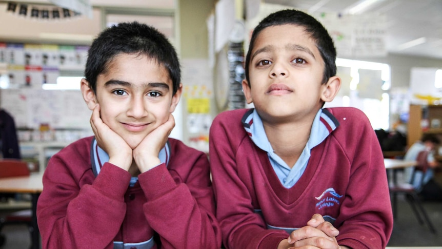 Year One students, Eesher and Atul sit at a classroom desk wearing school uniforms.