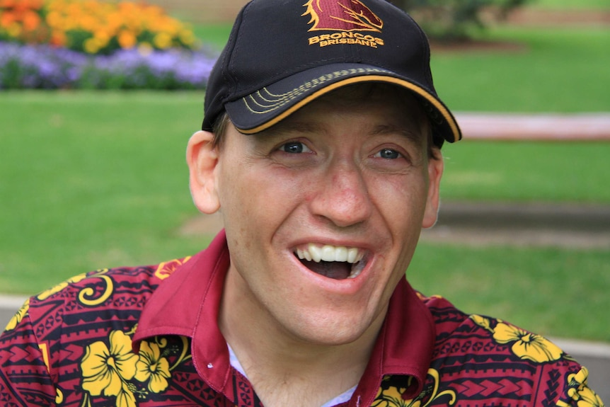 A man wearing a Brisbane Broncos cap and shirt sits smiling in a park.