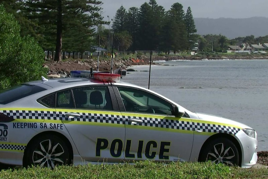 A police car in front of a rocky shore and sea