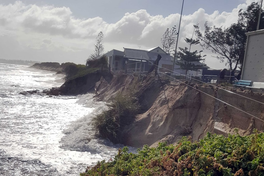 Water is lapping against the side of a major drop off at the beach, metres from buildings.