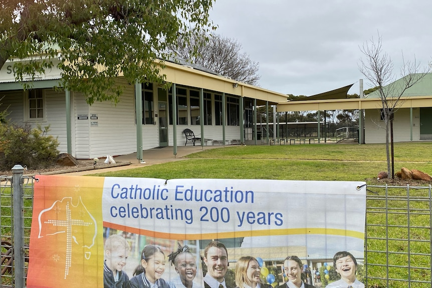 """The view of a white wooden building. A sign on a fence reads """"Catholic Education celebrating 200 yeras"""""""