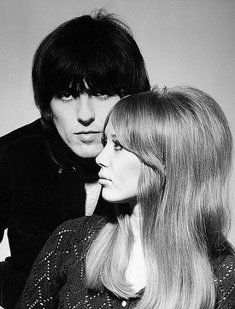 A man with black hair poses close to a women with blonde hair in a black and white photograph