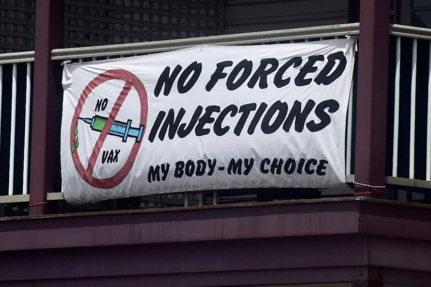 Along the main street of Mullumbimby, a sign reads 'no forced injections'.