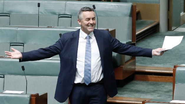 Darren Chester, wearing a dark suit, stands up in Parliament with his arms outstretched and a big grin on his face.
