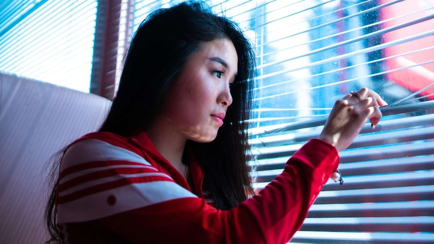 A young woman is looking through vertical blind on a window, like she's a bit anxious to go outside.