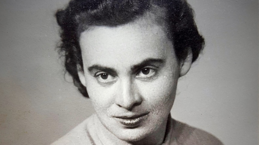 A vintage portrait of a woman looking at the camera with dark brown eyes and dark hair.