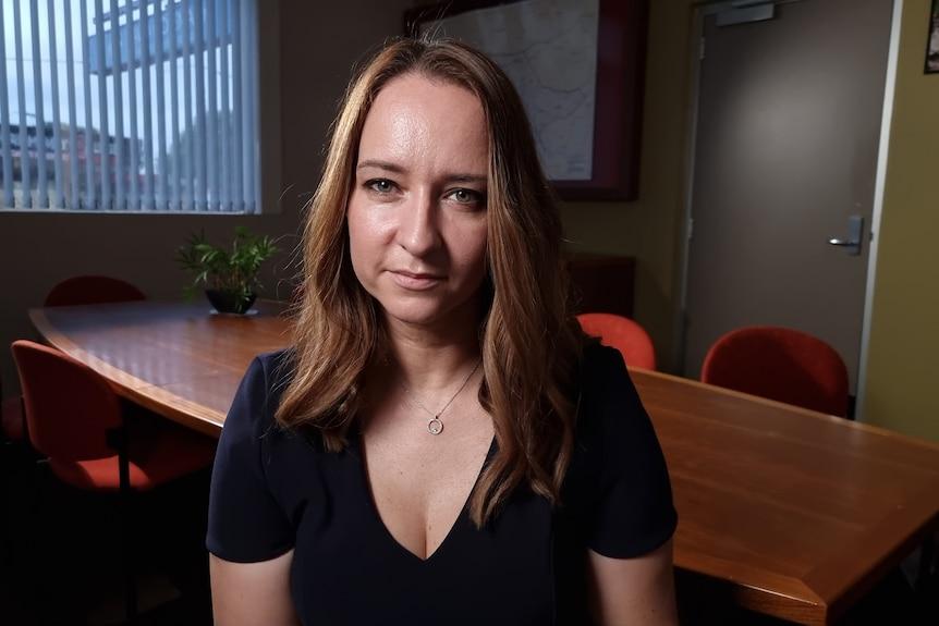 A woman wearing a dark t-shirt looking at the camera.