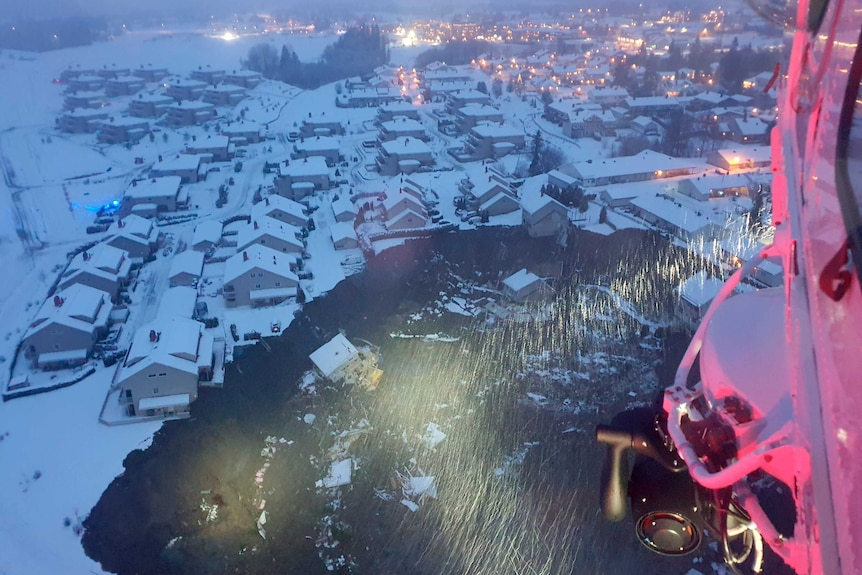 A black hole at the lower half of the photo is surrounded by houses and buildings covered in snow.