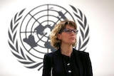 Agnes Callamard wears a black blazer and shirt while standing in front of a large black UN logo on a white wall.