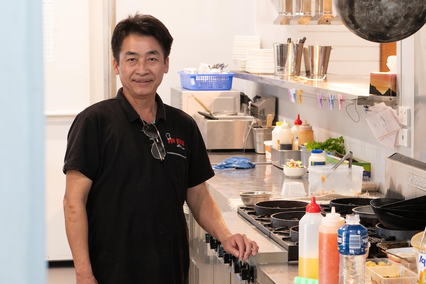 A middle-aged man stands in a commercial kitchen.