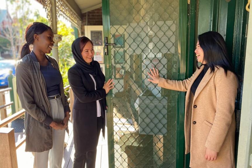 Three women stand at an open door smiling.