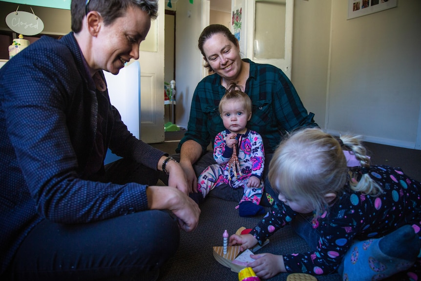 two women sitting on the floor, playing with their toddler and baby