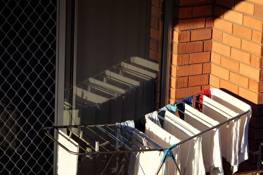 A clothes rack on a small balcony for a story about how often you should change your sheets.