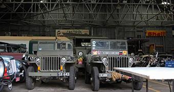 Old jeeps inside a hangar.
