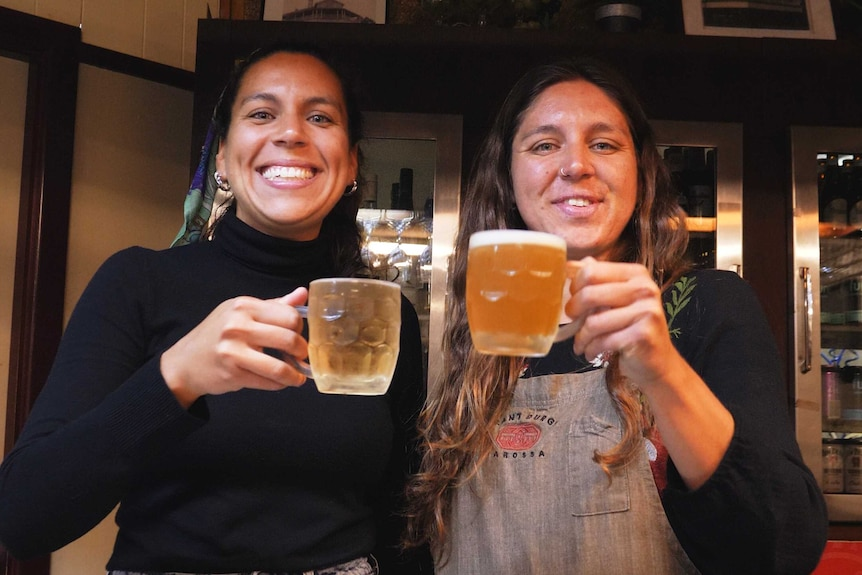 Two women with big grins hold up two glasses of beer in celebration.