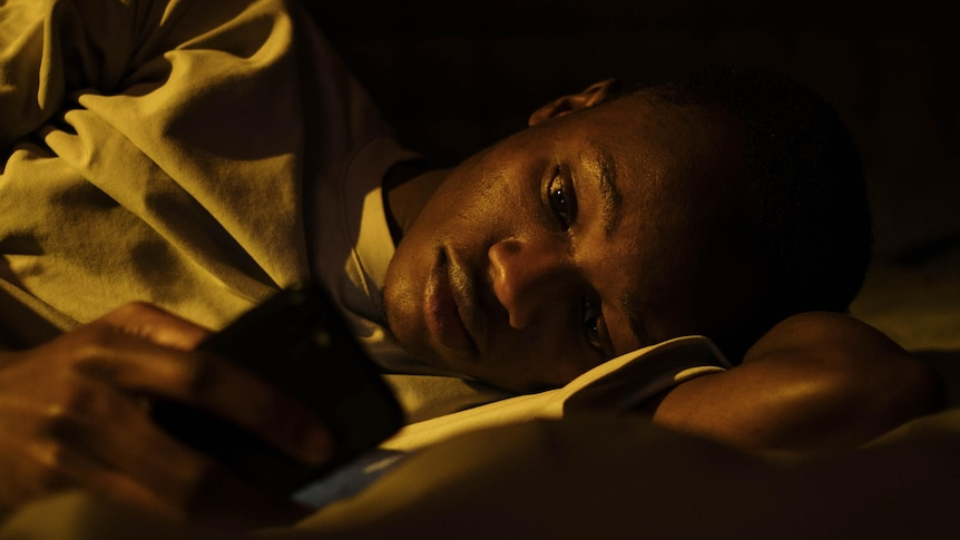 A man lays on his side in the dark illuminated by his phone light.