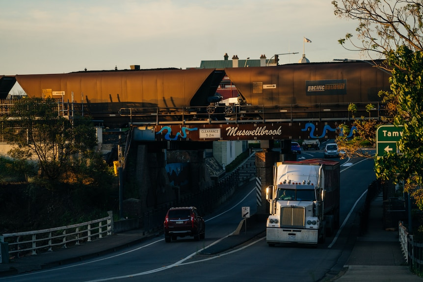 A coal train driving over a bridge with trucks driving underneath.