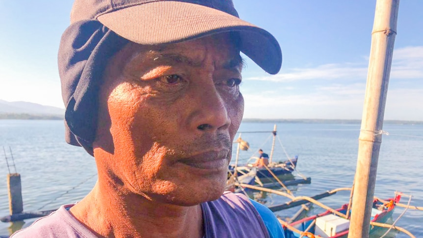 A man wearing a cap and shirt looks away from camera in front of a boat on the dock.