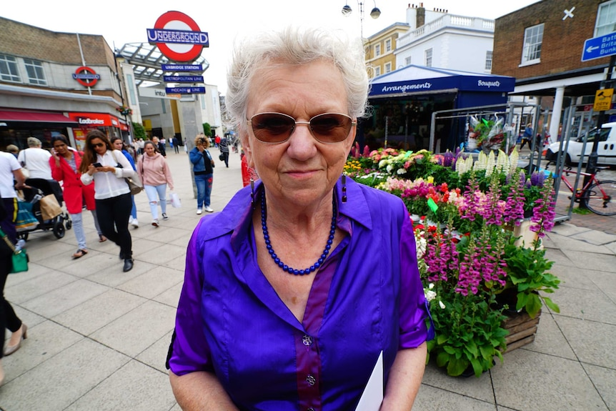 An older woman in a purple top standing next to a London tube station