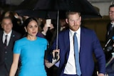 Prince Harry and Meghan, the Duke and Duchess of Sussex walk side by side holding an umbrella.