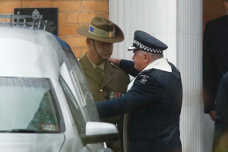 A man dressed in a police uniform hugs a man in a Defence Department uniform near a hearse.
