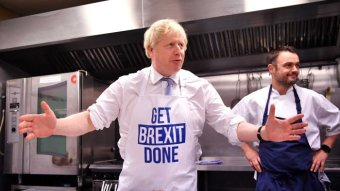A man in a 'Get Brexit done' apron stands in a kitchen