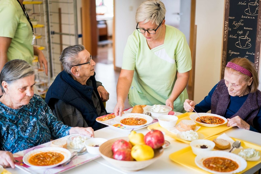 A staff member serves food to a group of nursing home residents at a dining table.