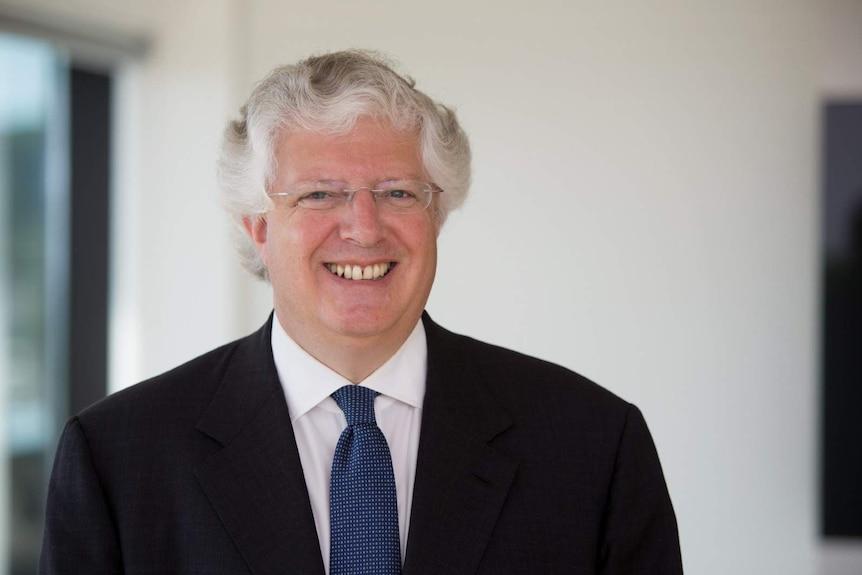 A photo of British investor Guy Hands smiling at a camera.