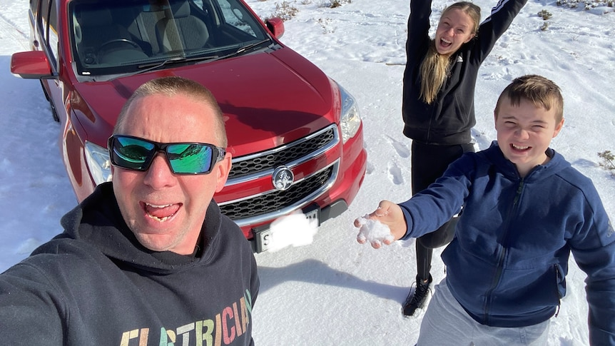 A man smiles at the camera in front of a red car. On the right a boy throws snow and a girl has her arms in the air.