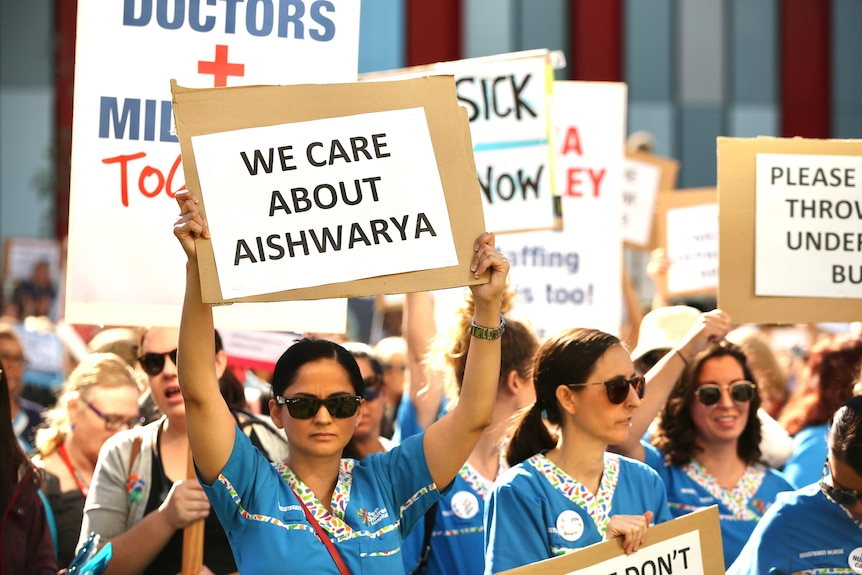A large rally held outside a hospital with nurses holding signs.
