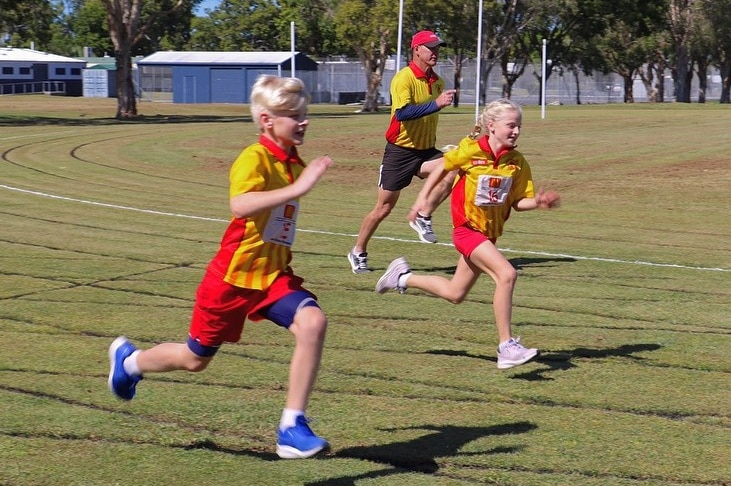 Two kids and a man run at a sports oval