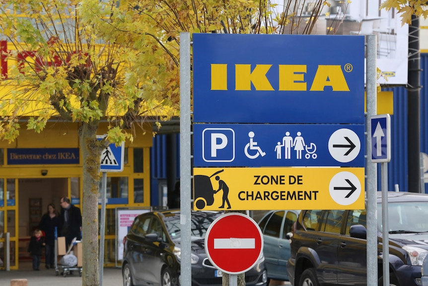 A large IKEA sign in the foreground as customers leave an IKEA store in Plaisir, west of Paris.