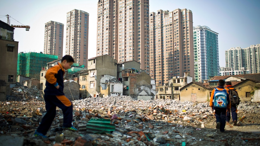 Three boys walk through rubble with a row of apartment towers along the skyline